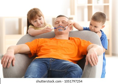 Little children painting their father's face while he sleeping. April fool's day prank