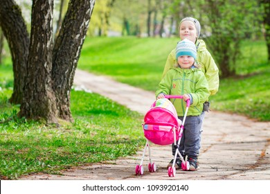 Little children play in yard with children's toy doll for dolls. boy and girl play game of children playing stroller in courtyard of house. Children's friendship. Kids with toy baby carriage
