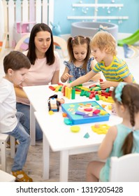 Little children playing different toys with teacher in daycare. Kids building color blocks. Educational toys for preschool and kindergarten pupils.