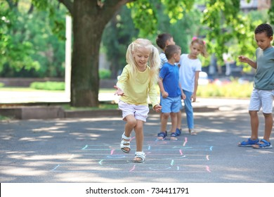 Little children playing hopscotch, outdoors