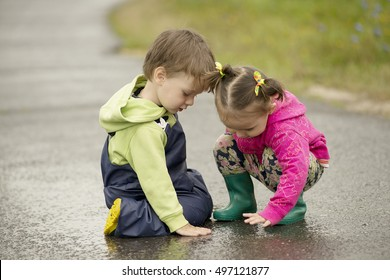 Little children playing in the puddles on the asphalt road