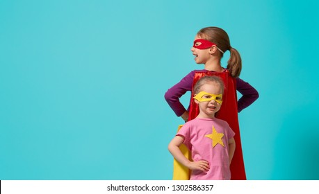 Little children are playing superhero. Kids on the background of bright wall. Girl power concept.