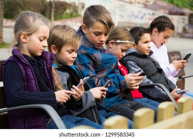 little children posing at urban street with mobile devices