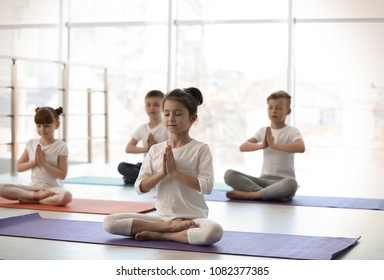 Little children practicing yoga in gym