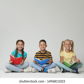 Little children reading books on grey background