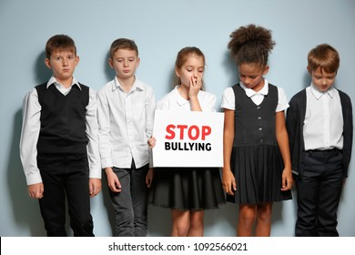 "Little children in school uniform holding sign ""Stop bullying"" on light background"