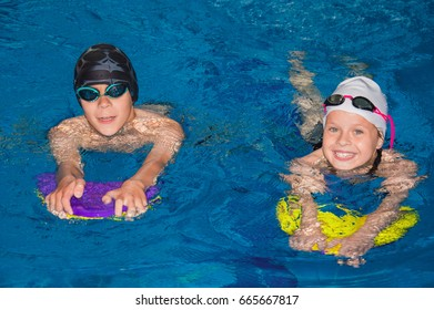 Little children swim in the pool under the guidance of a coach