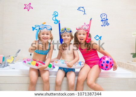 0b52fc386541c Little children in swimsuits and diving equipmen play in the bathroom like  in the sea