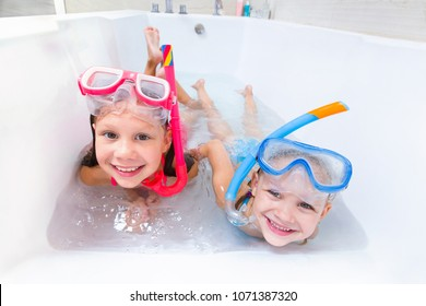 Little children in swimsuits play in the bathroom like in the sea