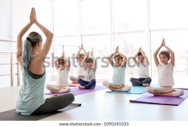 Kleine Kinder und ihr Lehrer, der Yoga im Fitnessraum praktiziert