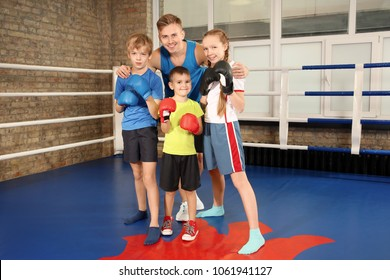Little children with their trainer on boxing ring