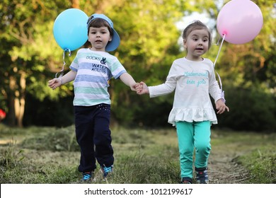 Little children are walking in a park with balloons