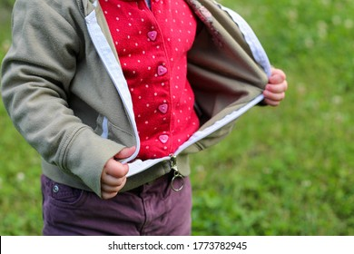Little children's handles unzip zip on a jacket on a background of blurred green grass
