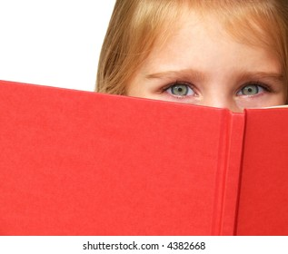 a little child's eyes looking over the top of a book