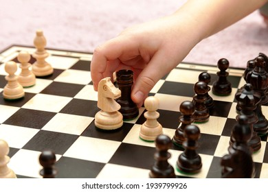Little childs hand moving a rook chess piece on a chessboard, closeup. Clever anonymous child making a move in a game of chess, capturing a piece. Intelligence, strategy, battle abstract concept