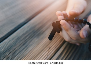 Little childs hands holding wooden rosary. Child praying