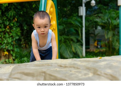 Little Chinese baby boy climbing up the stone in outdoor playground