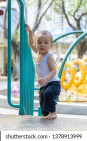 Little Chinese baby boy walking up the stairs with handrail in outdoor playground