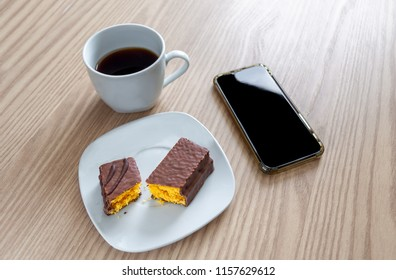 Little chocolate cake and a coffee cup on a wood table along with a smartphone