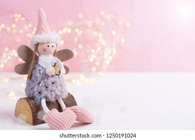 Little Christmas fairy  and fairy lights on white background against pink wall. Winter holidays, Christmas, New Year concept. Place for text.