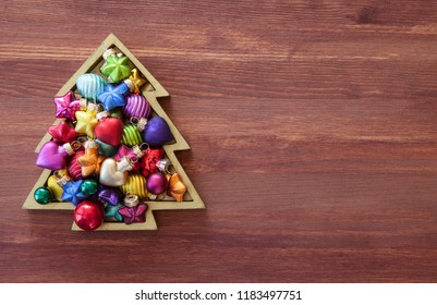 Little christmas tree with colorful baubles on wooden background