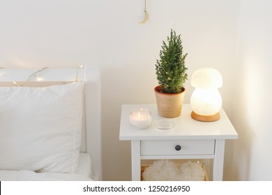 Little christmas tree in a pot with led garland lights, night salt lamp and candle on bedside table. New year winter home interior decor. Christmas holiday decorations. White stylish cozy bedroom.