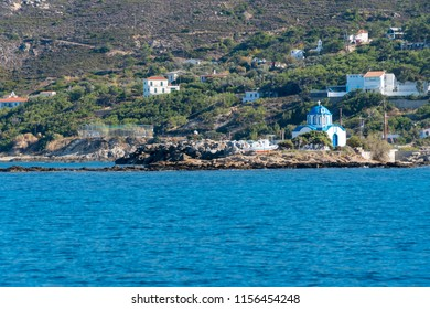 little church at the sea side of greek island ikaria. There is traditional boat in front of church