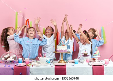 little cildren rejoicing at flying confetti, fun, joy, happiness, isolated pink background