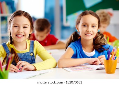 Little classmates smiling at the camera while sitting at the desk