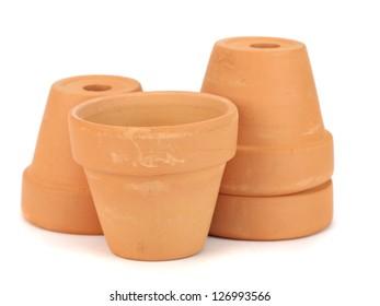 Little clay flowerpots on white background