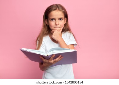 little clever girl touching her chin , going to read a book, kid being puzzled with the plot of story, hobby, lifestyle, free time, spare time. isolated pink background, studio shot