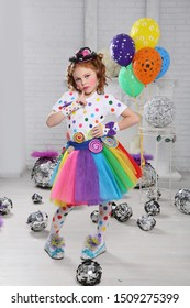 Little clown with balloons. A girl with red hair with bright makeup and colorful clothes plays a clown . The white room . posing standing .