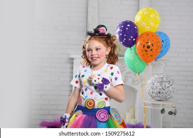 Little clown with balloons. A girl with red hair with bright makeup and colorful clothes plays a clown . The white room . authentic smile .