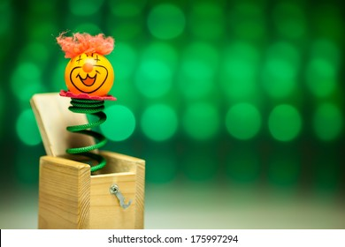 Little clown ping pong welcome surprise from wood box with blue blurry circle background