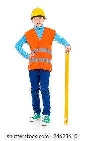 Little construction worker posing with a spirit level. Young boy in yellow hard hat and orange reflective vest posing with a spirit level. Full length studio shot isolated on white.