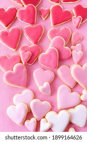 Little cookie hearts with pink icing on a pink background