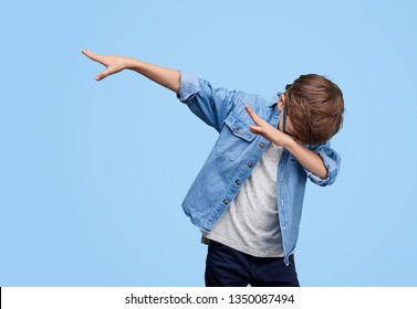 Little cool boy in glasses and denim jacket dabbing while posing on blue background