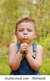 Little Country Boy Blows on Dandelion to make a Wish