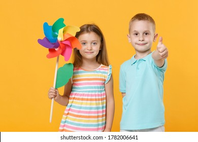 Little couple kids boy girl 5-6 years old in blue pink clothes shirt dress posing have fun isolated on yellow background children studio portrait. People childhood lifestyle concept hold toy windmill.