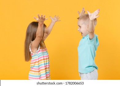 Little couple kids boy girl 5-6 years old in blue pink clothes shirt dress posing have fun isolated on yellow background children studio portrait. People childhood lifestyle concept raised hands up.