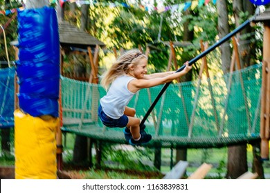 Little courageous blond scandinavian girl riding on a bungee swing on the playground of the park in the summer sunny day.