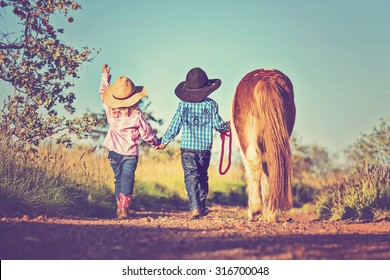 Little cowboy and cowgirl walking pony
