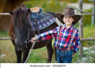 The little cowboy hat holding a black horse