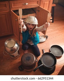 A little creative girl is pretending to drum music on pots and pans in the kitchen for a fun childhood lifestyle concept.