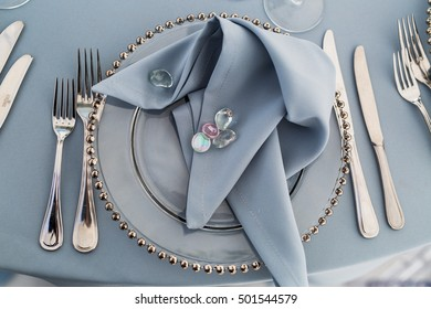 Little crystal stones put over blue serviette which lies on glass dinner plate