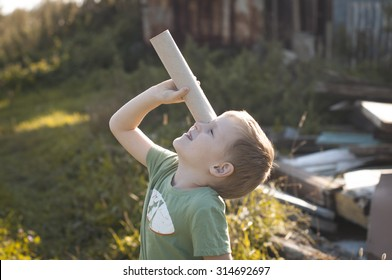 Little curious explorer, boy looking at skies through the cardboard spyglass