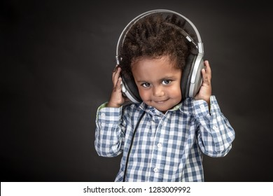 Little curly African-American baby boy with cute smile wearing headphones, sweet child having fun and listening favourite music, black background