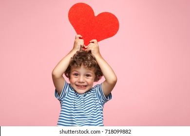 Little curly boy in t-shirt holding red heart shaped application and looking at camera happily on pink.