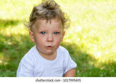 little curly boy in a white t-shirt cries in the street in the summer, closeup