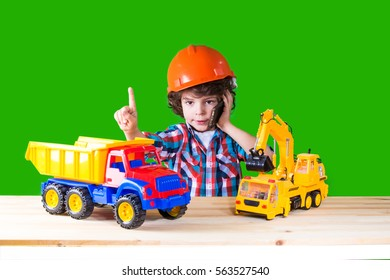 Little curly foreman indicates the index finger, talking on the phone next to the toy construction equipment. Close-up. Green background.